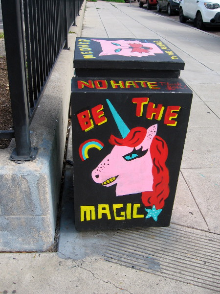 A rainbow and fierce pink unicorn painted on a utility box. BE THE MAGIC