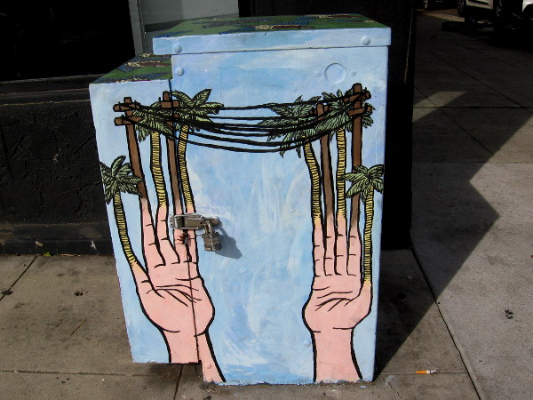 The fingers painted on this electrical box transform into palm trees and telephone poles!