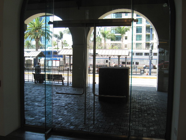 Looking west out glass doors at the Figi Family Concourse and trolley and train platforms at Santa Fe Depot.