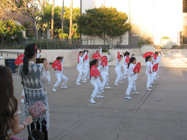 Kids representing the Confucius Institute perform kung fu fan moves in front of the Timken Museum of Art.