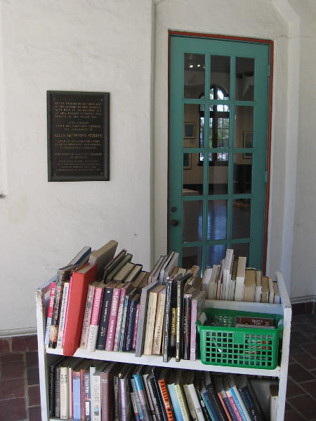 A library cart full of books entices passersby.