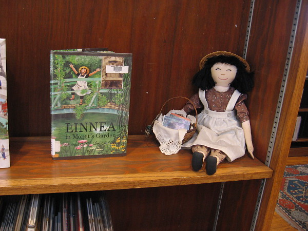 Linnea doll on shelf by the book Linnea in Monet's Garden.