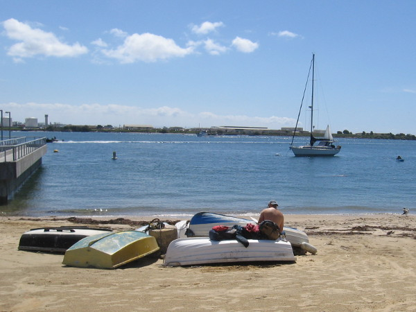 Someone hangs out nearby, sitting among beached dinghies.