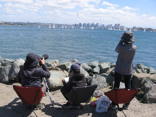 Some people by the rocky shore watch even more distant sailboats with binoculars.