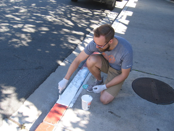 Volunteer on a sidewalk in Liberty Station applies a new coat of paint on the curb above a storm drain.