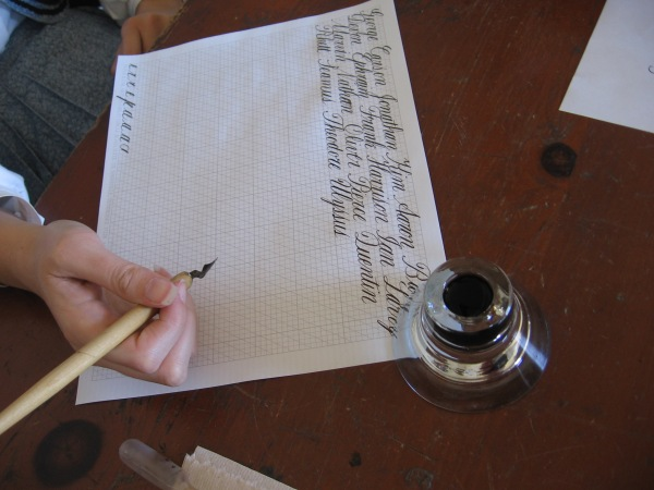 Showing how to write fancy letters with a quill and inkwell!