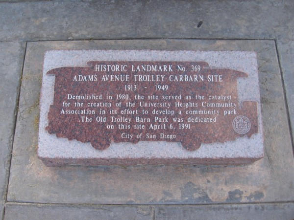 Plaque at base of post reads: HISTORIC LANDMARK No. 369 - ADAMS AVENUE TROLLEY CARBARN SITE 1913 - 1949 . . . The Old Trolley Barn Park was dedicated on this site April 6, 1991.