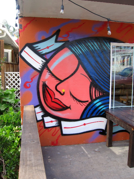 A bold, contented face painted by the entrance to Dia Del Cafe.