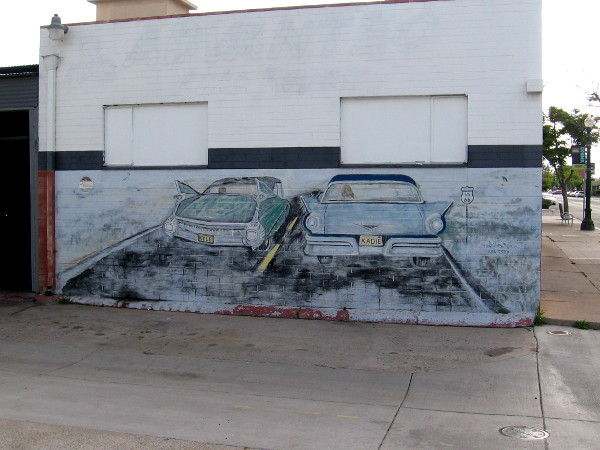 Faded mural depicting two classic cars, next to a repair bay at Advantec Auto Repair.