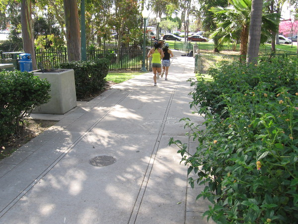 People jog along a walkway which features tracks that wind through the park like the old trolley line.