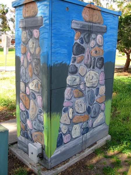 An electrical box at the edge of the park is painted like a cobblestone post, one of the symbols of University Heights.