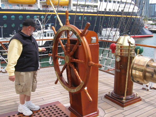 A visitor aboard the BAP Unión checks out the impressive ship's wheel.