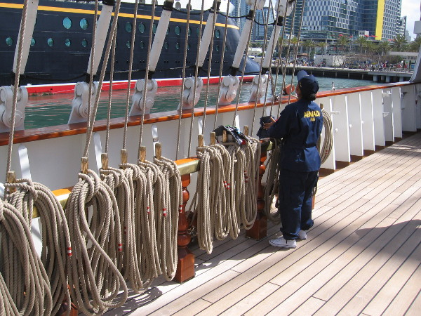 A crew member on deck tends to some ropes.