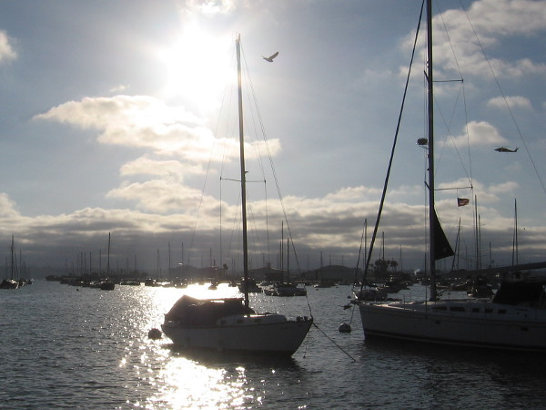 Sun shines through late clouds, splashing light across San Diego Bay in its peaceful Crescent Area.