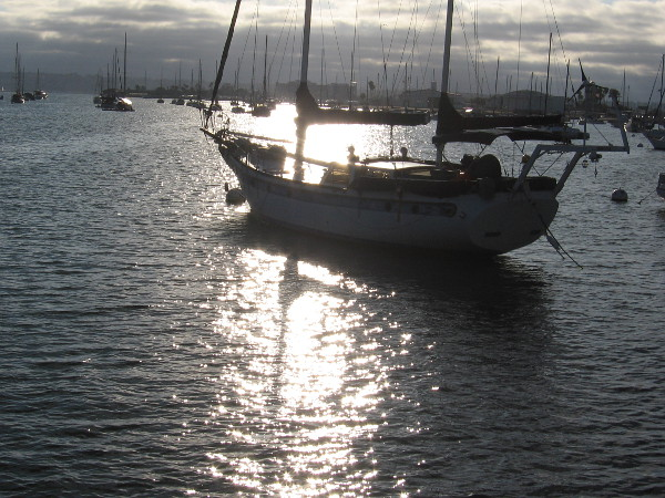 Boat moored in San Diego Bay becomes darkly mysterious in the late light.