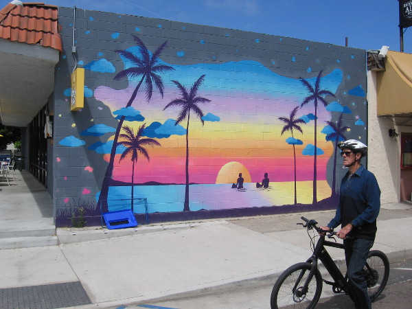 Someone rides their bike down Highway 101 past this beach sunset mural by @CloeHakakian