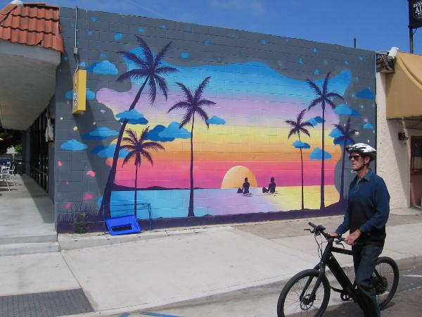 Someone rides their bike down Highway 101 past this beach sunset mural by @CloeHakakian