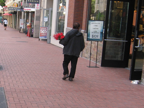 Carrying a bouquet of red roses.
