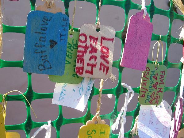 Many messages dangle from the Love Wall. Love each other.