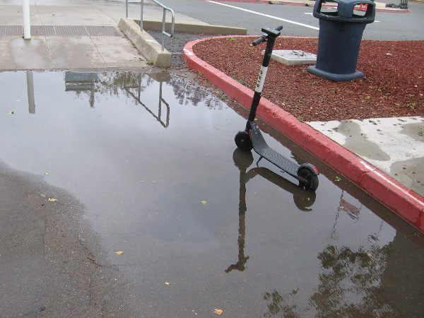 A scooter and its reflection in another puddle.