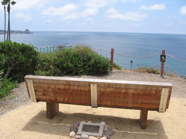 Bench overlooks the wide blue ocean.
