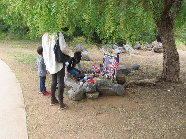 A family in Escondido's Kit Carson Park pauses to gaze at a small memorial.