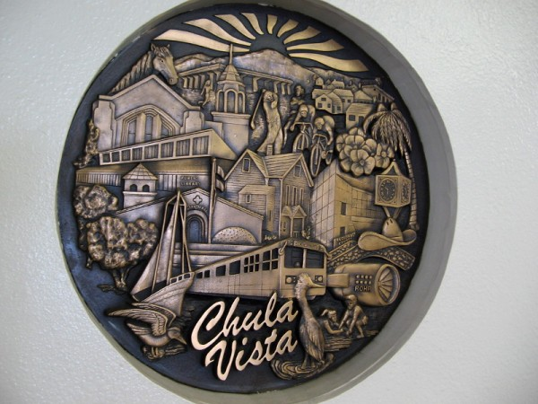 Large sculpted medallion in a wall near the entrance to the Chula Vista Public Library. Scenes depicted include Rohr Aircraft Company, the San Diego Country Club, home of golf legend Billy Casper.