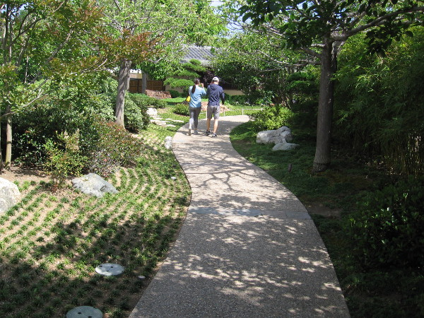 A couple moves forward down a winding path through the Japanese Friendship Garden.