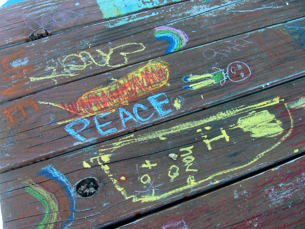 Kids created some chalk art on a picnic table.