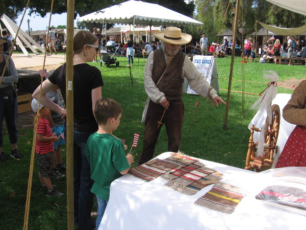 A family at Old Town's Fourth of July event learns all about spinning yarn.