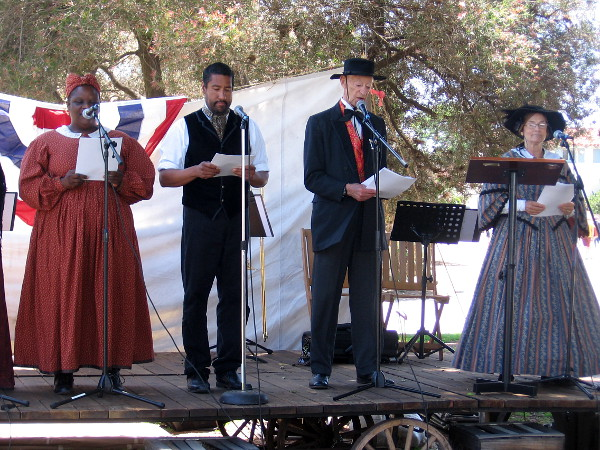Diverse people in period costume read segments of the Declaration of Independence.