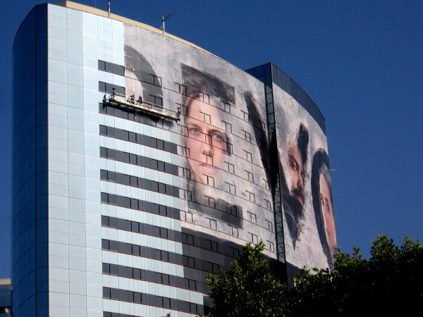Workers apply large format printed wrap material to the side of one tower.