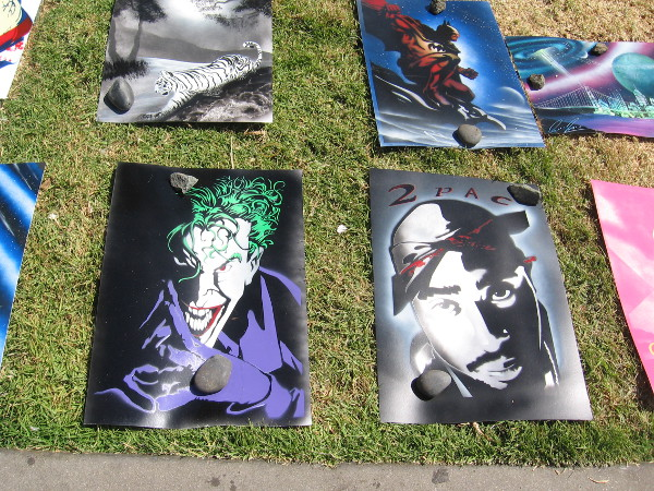 An artist had spray paint art creations on the grass by a walkway.