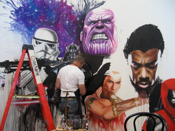 Rob Prior works on a mural that includes several well-known pop culture characters.
