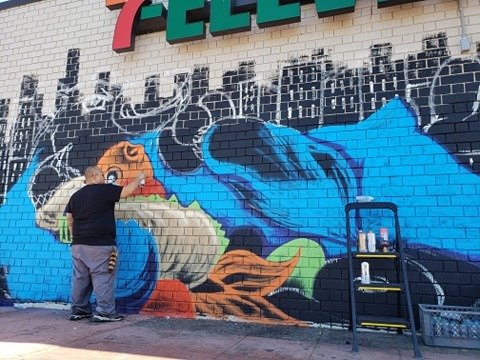 GMONIK works on the City Heights mural Bare Necessities. Photo credit GMONIK.