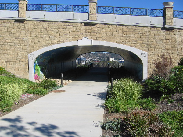 View of the pedestrian tunnel that passes under Via Alta in Civita Park. The mural inside depicts many wonderful places around San Diego.