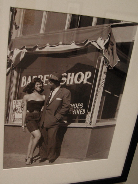 Barbershop, Los Angeles, 1956, Harry Adams. Photographer Harry Adams stands with a young woman in front of his barbershop.