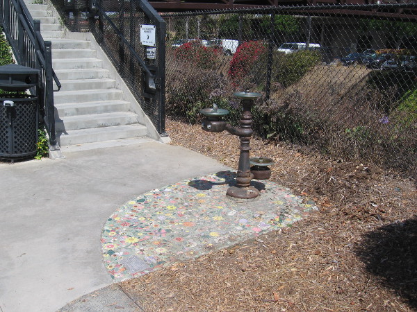 A water fountain near steps to the Dahlia Drive pedestrian bridge that spans the train tracks. The fountain stands above colorful mosaics.
