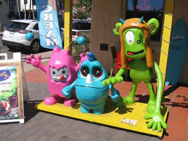 Three happy, silly creatures greet fun-loving people in front of Dr. Freeze Amazing Desserts!