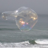 Conjuring magic bubbles by the ocean.