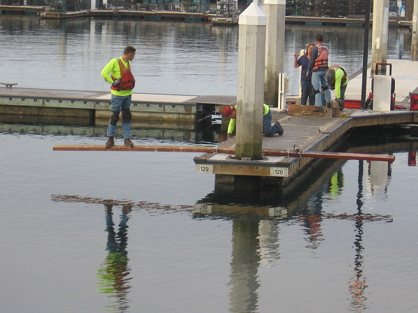 A worker casually stands on the plank above the water. An odd and mysterious image!