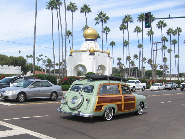 A woody with surfboard heads north along old Coast Highway 101 past one of the exotic Self-Realization Fellowship Golden Lotus Towers.