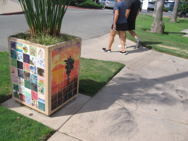 People walk past another planter with cool tile art.
