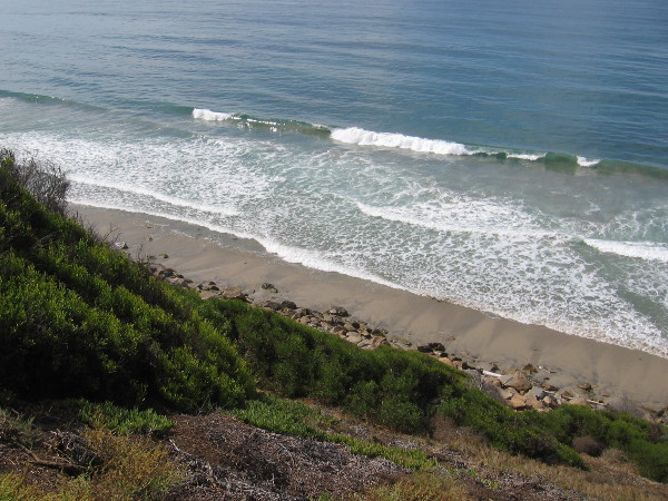 The surging Pacific Ocean and the narrow beach below.