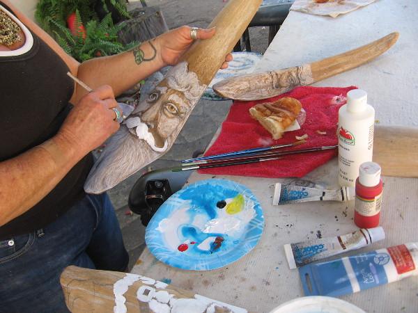 Artist paints a face at the Spanish Village Art Center.