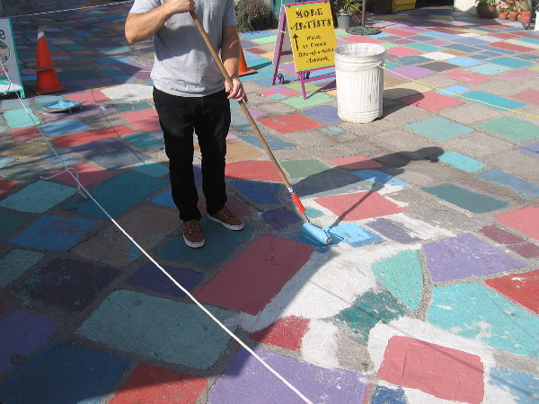 Painting the colored tile patio of Spanish Village.