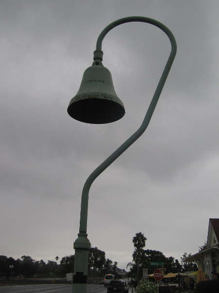 An El Camino Real bell above the sidewalk along Coast Highway 101 in Leucadia.