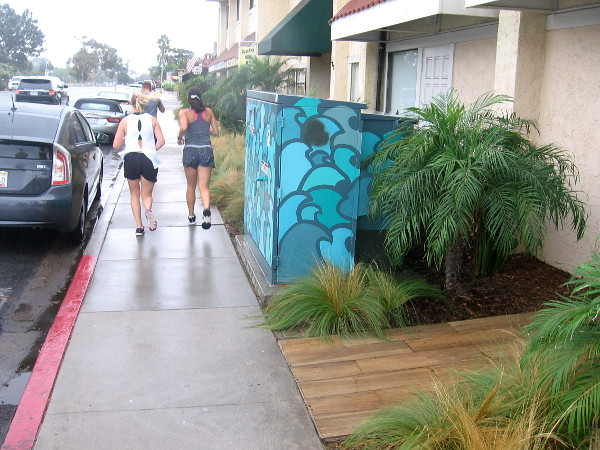 Joggers heading down the damp sidewalk near some art on electrical boxes.