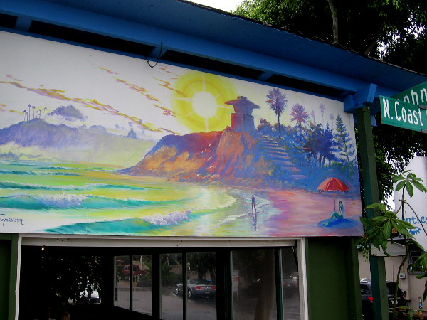 Another cool mural above a window with a colorful beach scene.