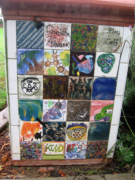A trashcan in the park features fun tile art.